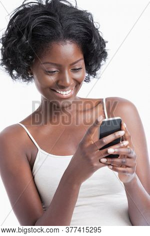 Happy young African American woman text messaging over white background