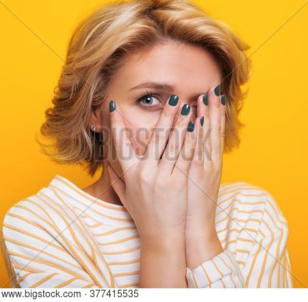 Scared Caucasian Woman Covering Her Face With Palms Looking At Camera And Posing On A Yellow Studio