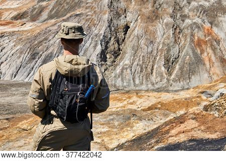 Male Geologist On An Expedition Among A Desert Ravine Landscape, View From The Back