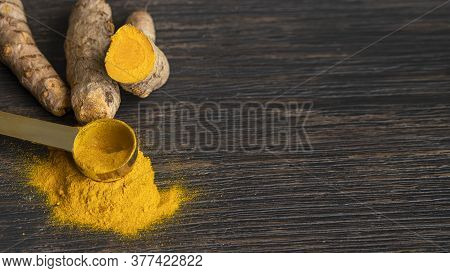 Turmeric  Roots And Turmeric Powder On Llarge Woodem Background With Copy Space. Tumeric Used As Spi