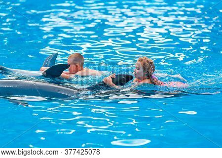 Happy Little Kids Swimming With Dolphins In Dolphinarium