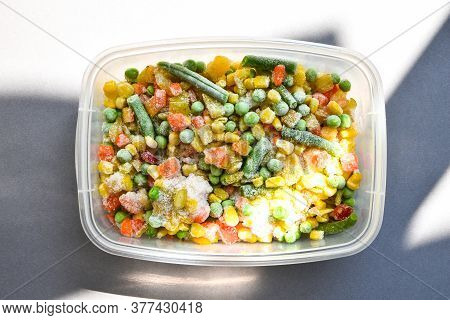 Frozen Mixed Vegetables In A Plastic Container For Long-term Storage With Deep Shadows. Deep Freezin