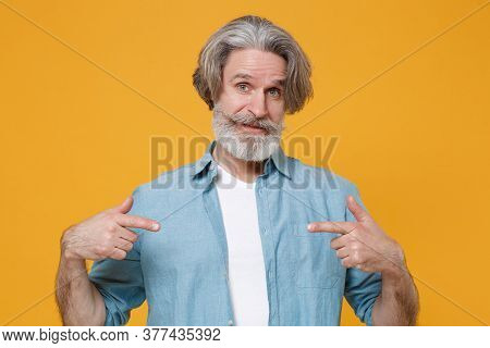Puzzled Elderly Gray-haired Mustache Bearded Man In Casual Blue Shirt Posing Isolated On Yellow Back
