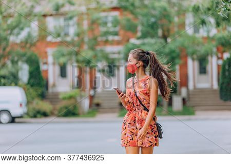 COVID-19 girl walking in city street wearing face mask. Mandatory wear Asian woman commuting using mobile phone. protection as prevention for coronavirus outside in city park summer. Corona virus.