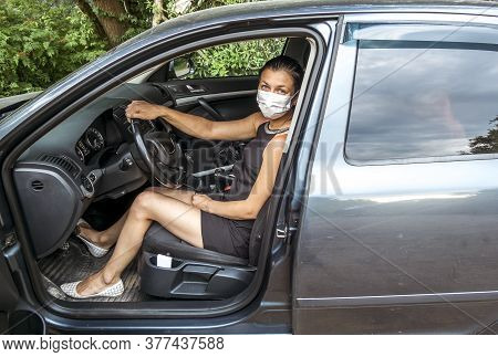 A Young Woman In A Medical Mask Sits Behind The Wheel Of A Car