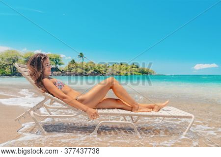 Hawaii beach relax happy beautiful young Asian natural beauty woman lying on lounger in water relaxing on summer vacation holidays.