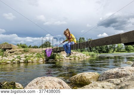 A Girl With A Net Sits On A Bridge Across A River On A Sunny Summer Day