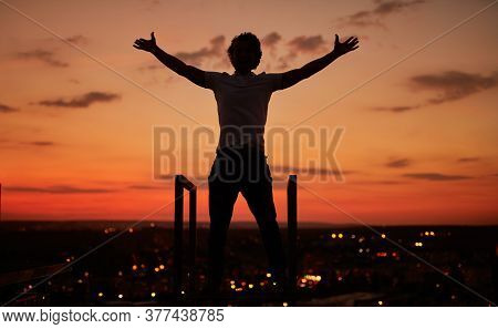 Silhouette Of Unrecognizable Guy With Outstretched Arms Standing On Rooftop And Enjoying Freedom On