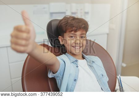 Lovely Cheerful Young Boy Smiling, Showing Thumbs Up Sitting In A Dental Chair. Adorable Little Boy