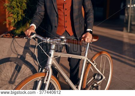 Crop Anonymous Fashionable Businessman In Classy Suit Standing With Bike On Sidewalk In Sunny Day In