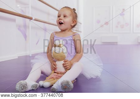 Happy Little Ballerina Girl Looking Excited, Sitting On The Floor At Ballet School, Holding Her Ball