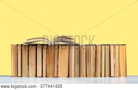 Open Hardback Book, Diary, Fanned Pages On Stack Of Books On White Table In Library. Books Stacking.