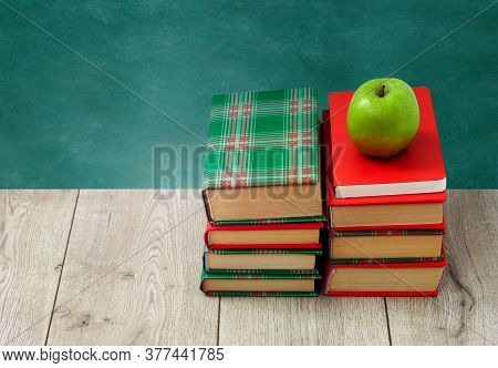 Back To School, Pile Of Books In Colorful Covers And Green Apple On Wooden Table With Empty Green Sc
