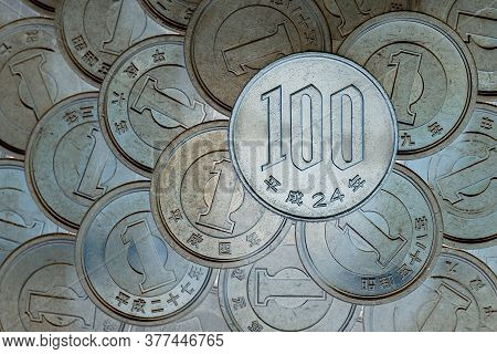 A Field Of Japanese Coins In 1 Yen, On It Lies A Coin Of 100 Yen. News About The Economy, Finances A