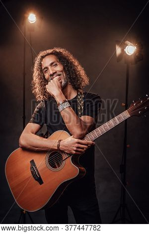 Middle Aged Hispanic Man Musician In Black T-shirt Holds Guitar On A Scene, Smiling And Looking On C