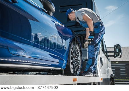 Car Repossession Worker Securing Vehicle On His Towing Truck. Vehicle Financing And Repo Company.