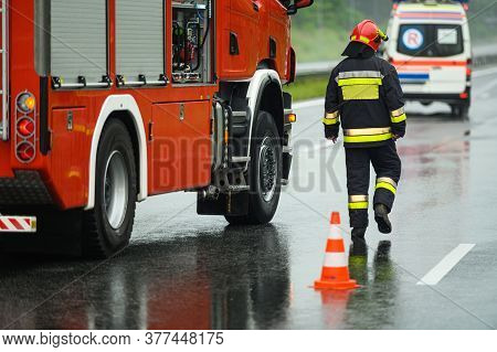 Highway Traffic Accident Site Firefighter Securing Traffic. Firetruck And Ambulance.
