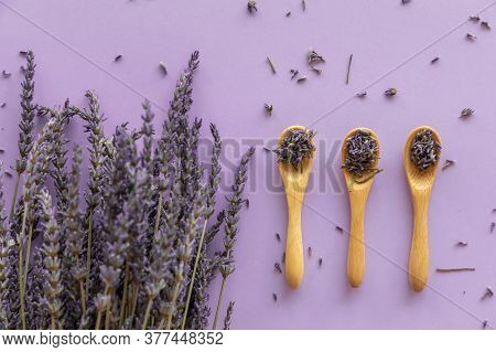 Dry Lavender Flower In Wooden Spoon And Lavender Bouquet On Violet Paper Background