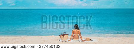 Beach summer vacation banner relaxing sunbathing woman lying on towel tanning alone panorama travel on blue ocean panoramic header crop.