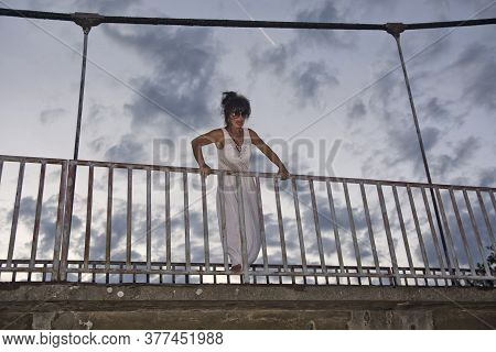 Woman At Dusk By The Bridge Railing