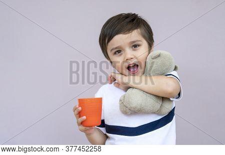 Studio Portrait Cute Little Boy Drinking Orange Juice From Plastic Glass On Light Purple Background,