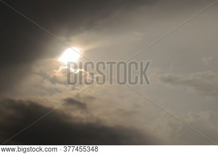 The Sun Peeks Out From Behind The Clouds After A Thunderstorm. Dark Gray Heavy Stormy Sky. Dramatic
