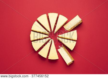 Creamy Cheesecake Sliced With Interior Section, Isolated On A Red Background. Top View Of Delicious