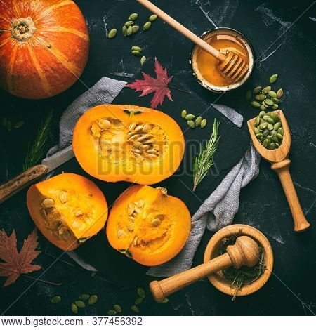 Raw Pumpkin With Herbs, Seeds And Honey On A Black Stone Background, Toned. Autumn Background. Thank