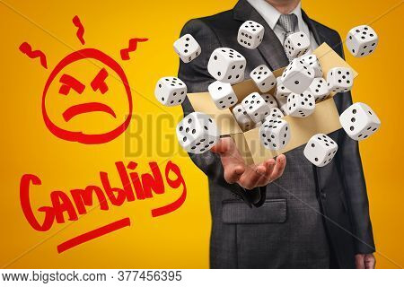 Businessman Holding Cardboard Box Filled With White Casino Dice And Gambling Sign On Yellow Backgrou