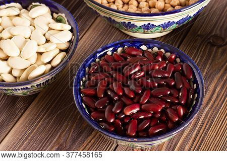 Red Beans In A Bowl Among Bowls Of Different Legume On Wooden Background. Close Up.