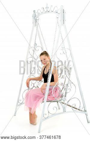 Portrait Of A Beautiful Girl Sitting On An Elegant Metal Swing, Blonde Swinging, Looking At Camera,