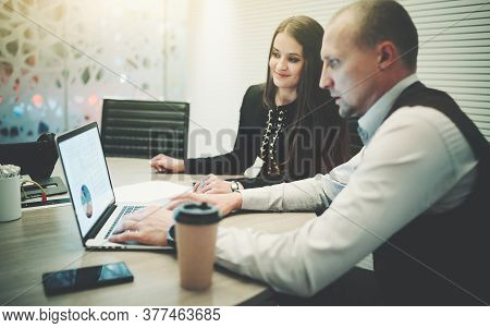 Business Colleagues Having A Meeting In A Boardroom: A Man Entrepreneur Is Showing His Female Partne