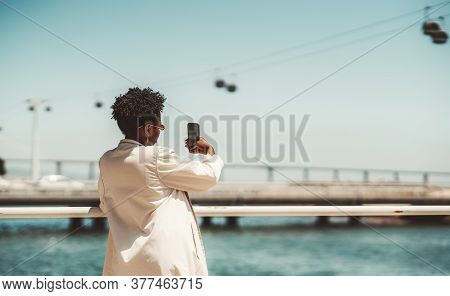 View From Behind Of A Young Black Female Tourist With A Curly Afro Hair, In A White Trench And Curly