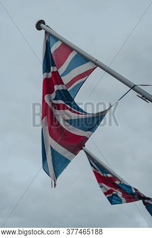 Union Jack Flags On On A Flagpole In Stow-on-the-wold, Cotswolds, Uk, Against A Gloomy Grey Sky, Sel