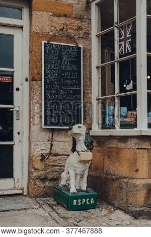 Stow-on-the-wold, Uk - July 6, 2020: Old Dog-shaped Rspca Charity Collection Box In From Of A Shop I
