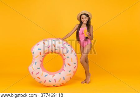 Enjoying Suntan And Vacation. Cheerful Small Girl In Swimsuit And Straw Hat. Pool Beach Fun. Child W