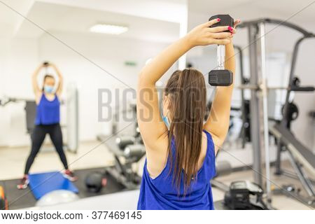 Woman with facemask training in gym, indoor. Female breathes deeply stock photo