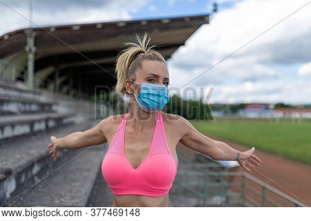 Woman takes off facemask after training or running on sports field. Female breathes deeply