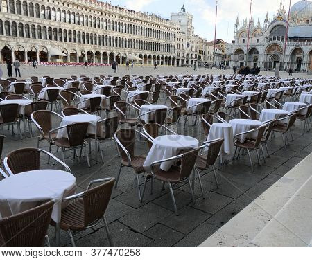 Vacant Tables With White Tablecloths Set Up In A Nearly Empty St. Marks Square In Venice