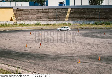 Car And Traffic Cones, Driving School Concept. Training Car Performs Exercises On Training Ground In