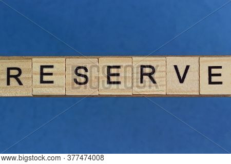 Text On Gray Word Reserve In Small Wooden Letters With Black Font On A Blue Background