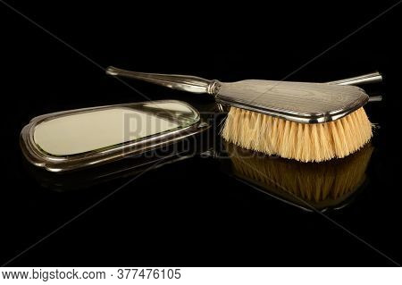 A Vintage Set Of A Handheld Sterling Silver Mirror And Hair Brush Isolated Over A Black Reflective S