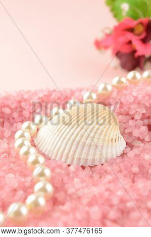 A Sea Shell And A String Of Pearls Lay Across A Bed Of Pink Bath Salts For A Warm Inviting Scene Wit