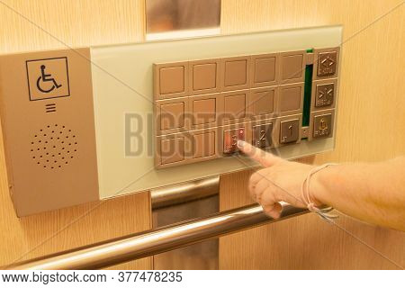 Female's Finger Pressing On Floor Number On Elevator Panel