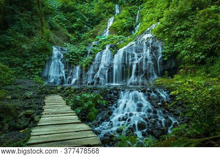 Amazing Landscape. Beautiful Hidden Waterfall In Tropical Rainforest. Wooden Bridge Across The River