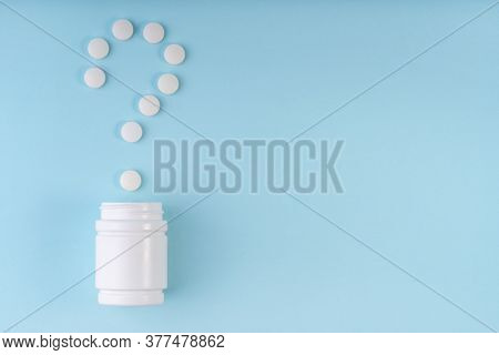 Question Sign, Mark From Pharmaceutical Medicine Pills. Creative Layout Of Tablets And Bottle On Blu
