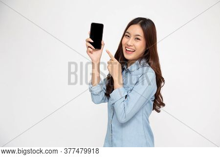 Portrait Of Asian Woman Showing Or Presenting Mobile Phone Application And Pointing Finger To Smartp