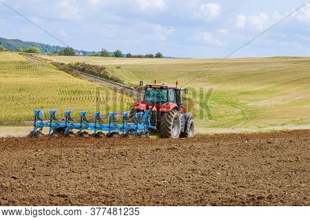 Plowing The Field. Large Plow On A Tractor. Tractor With Agricultural Attachment.