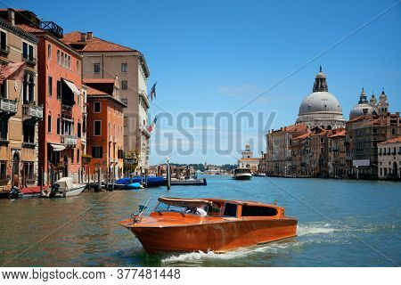 Busy Venice canal and Church Santa Maria della Salute in Italy.