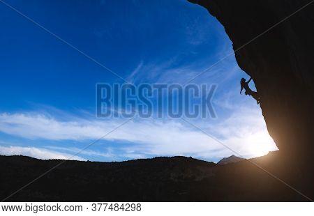 Silhouette Of A Rock Climber Climbing An Arch Shaped Rock, A Woman Overcomes A Difficult Climbing Ro